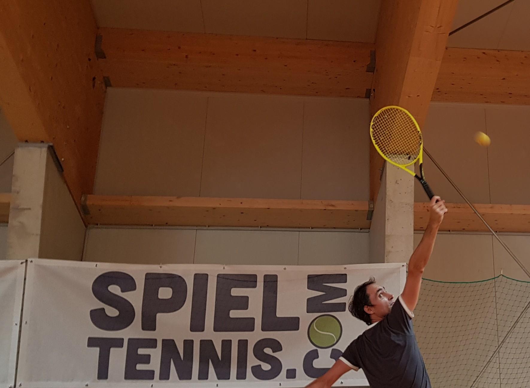 Tennislehrer zeigt Rückhandsmash